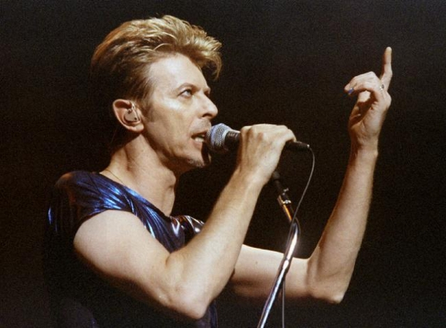 Singer David Bowie gestures as he performs one of the the first songs of a six-week concert tour of North America while appearing with the band Nine Inch Nails at the Meadows Music Theater in Hart ...