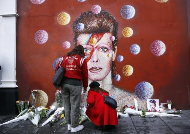 Two women stop at a mural of David Bowie in Brixton, south London, January 11, 2016. REUTERS/Stefan Wermuth