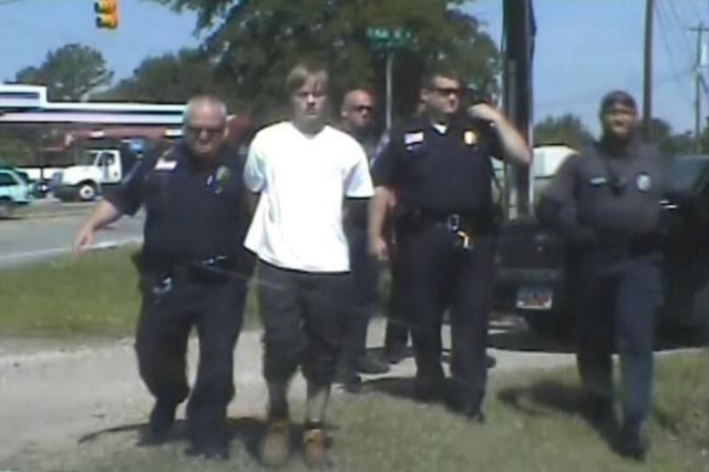 South Carolina shooting suspect Dylann Roof (C) is escorted by police after being detained in Shelby, North Carolina June 18, in this still image from a dash cam video released by the Shelby Polic ...