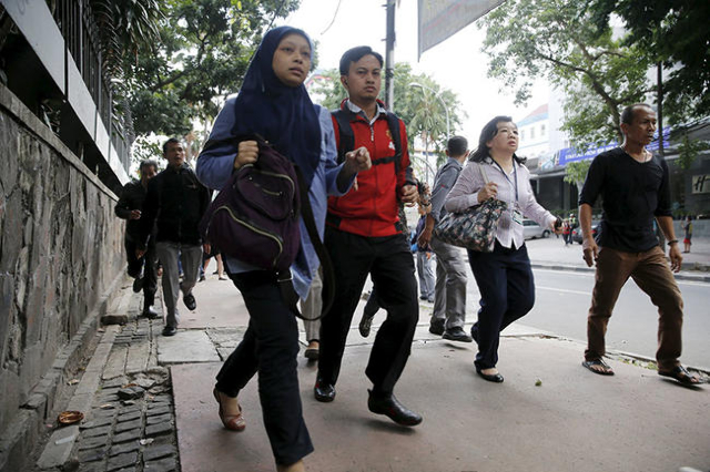 Indonesian workers run as they are evacuated from their office at Thamrin business district in Jakarta January 14, 2016.  Several explosions went off and gunfire broke out in the center of the Ind ...