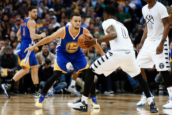Jan 13, 2016; Denver, CO, USA; Denver Nuggets guard Emmanuel Mudiay (0) dribbles the ball against Golden State Warriors guard Stephen Curry (30) in the fourth quarter at the Pepsi Center. The Nugg ...