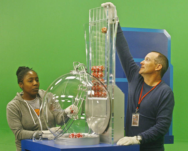 Draw Managers Robert Bechtol (R) and Tiffany Hicks (L) load Powerball numbers before the drawing at the Florida Lottery studio in Tallahassee, Florida January 13, 2016. They are using gloves to pr ...