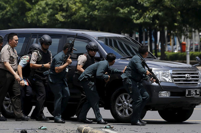 Indonesian police hold rifles while walking behind a car for protection in Jakarta January 14, 2016.  Several explosions went off and gunfire broke out in the center of the Indonesian capital on T ...