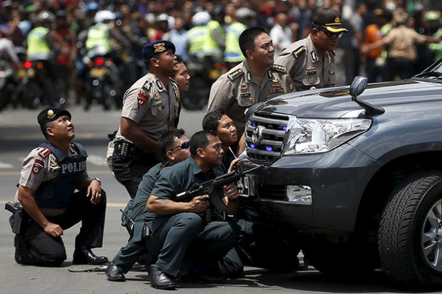 Police officers react near the site of a blast in Jakarta, Indonesia, January 14, 2016. Several explosions went off and gunfire broke out in the centre of the Indonesian capital on Thursday and po ...