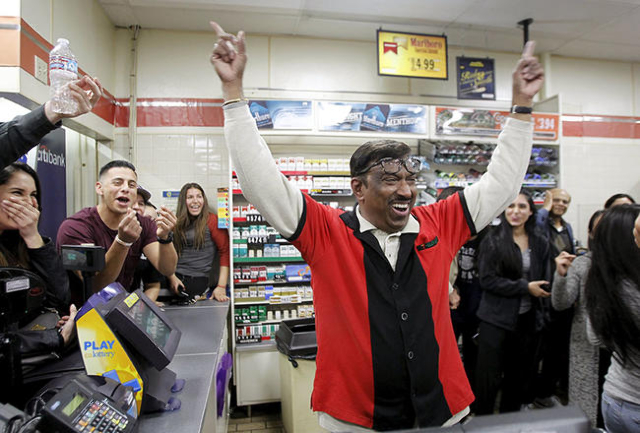 7-Eleven store clerk M. Faroqui celebrates after selling a winning Powerball ticket was sold is shown in Chino Hills, California January 13, 2016. A winning ticket was sold there for the massive $ ...