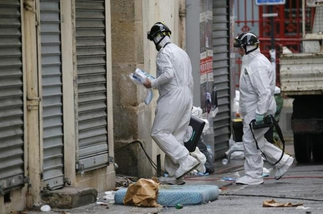 Forensic experts enter a building as they work on the scene in Saint-Denis, near Paris, France, November 19, 2015 the day after a police raid to catch fugitives from Friday night's deadly at ...