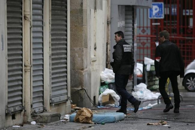 A member of French judicial police and a French plainclothes policeman walk outside a building in Saint-Denis, near Paris, France, November 19, 2015 the day after a police raid to catch fugitives  ...