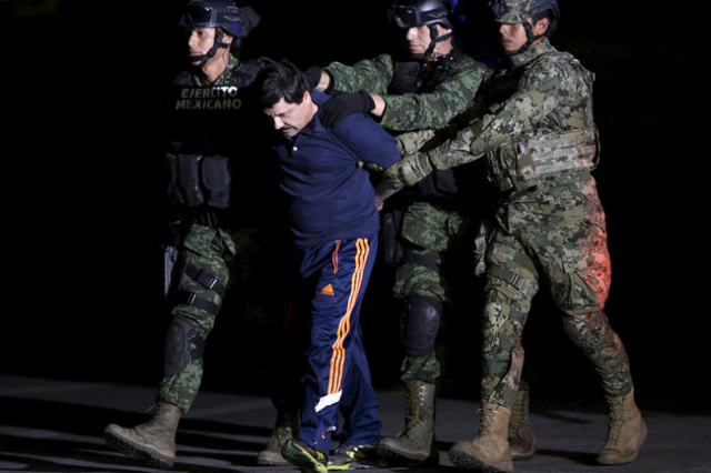 "Recaptured drug lord Joaquin ""El Chapo"" Guzman is escorted by soldiers at the hangar belonging to the office of the Attorney General in Mexico City, Mexico January 8, 2016. REUTERS/Henry ..."