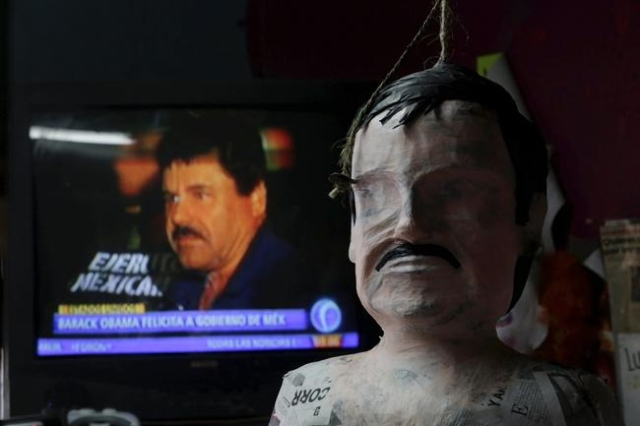 "A pinata in progress depicting the drug lord Joaquin ""El Chapo"" Guzman is seen in front of a television showing a news bulletin of him, at a workshop in Reynosa, in Tamaulipas state, Mex ..."
