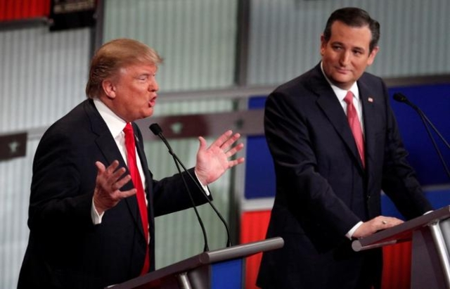 Republican U.S. presidential candidate businessman Donald Trump (L) speaks as rival candidate Senator Ted Cruz looks on during the Fox Business Network Republican presidential candidates debate in ...