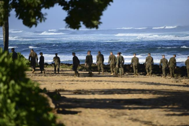 A group of Marines walk the beach outside the Haleiwa Incident Command Post in Haleiwa, Hawaii, during search efforts for 12 missing Marines, in this handout photo taken Jan. 18, 2016. (U.S. Coast ...