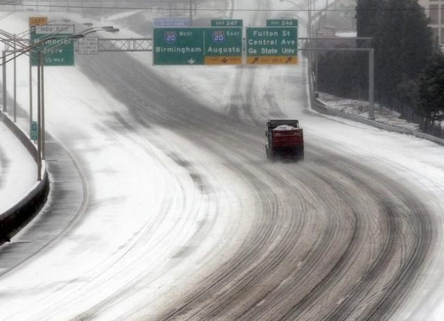 A sand truck dumping salt and sand on a downtown expressway as drivers heed advice to not drive during an ice storm in Atlanta, Georgia, February 12, 2014. (Tami Chappell/Reuters)
