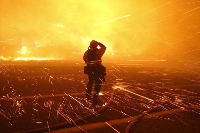 Fire photographer Tod Sudmeier gets hit with flying embers from strong winds at the Solimar brush fire that started early Saturday morning in Ventura County, California December 26, 2015. (Gene Bl ...