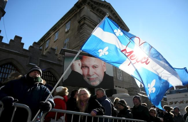 Celine Dion fan Adam St-Couer holds a Quebec flag as he waits in line to be admitted for the funeral for Rene Angelil at Notre Dame Basilica in Montreal, Jan. 22, 2016. (Christinne Muschi/Reuters)