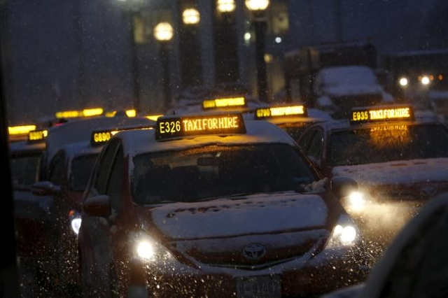 Taxis wait for fares in the snow at Union Station in Washington January 22, 2016. REUTERS/Jonathan Ernst