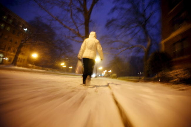 A woman walks in the snow after a winter storm arrived in Washington January 22, 2016. The leading edge of a monster snowstorm arrived on Friday afternoon in Washington, threatening to dump as man ...
