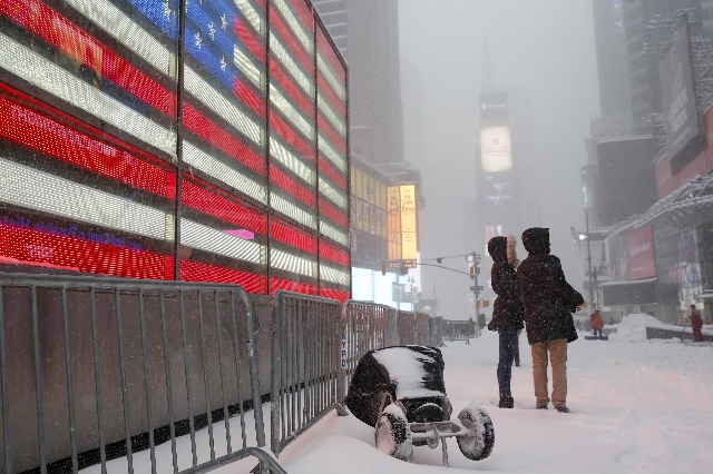 People stand during a snowstorm at Times Square in the Manhattan borough of  New York January 23, 2016. A winter storm dumped nearly 2 feet (58 cm) of snow on the suburbs of Washington, D.C., on S ...
