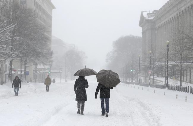 People walk down 15th Street snow during a winter storm in Washington January 23, 2016. A winter storm dumped nearly 2 feet (58 cm) of snow on the suburbs of Washington, D.C., on Saturday before m ...