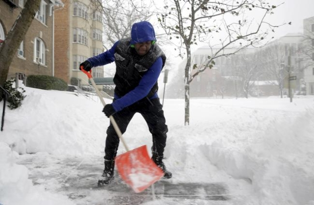 Anthony Williams shovels his walk during a winter storm in the Capitol Hill neighborhood in Washington January 23, 2016. A winter storm dumped nearly 2 feet (58 cm) of snow on the suburbs of Washi ...