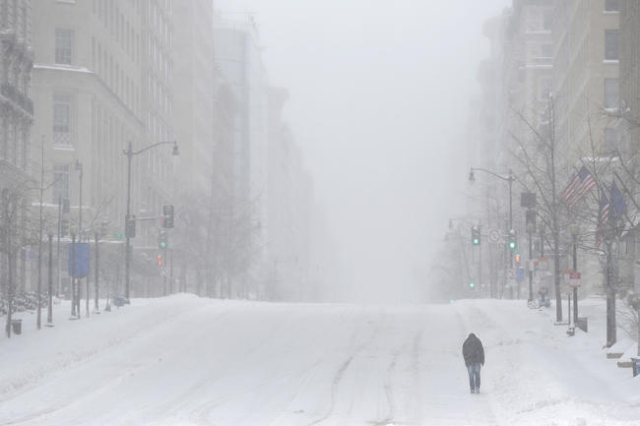 A man walks up 14th Street during a winter storm in Washington January 23, 2016. A winter storm dumped nearly 2 feet (58 cm) of snow on the suburbs of Washington, D.C., on Saturday before moving o ...