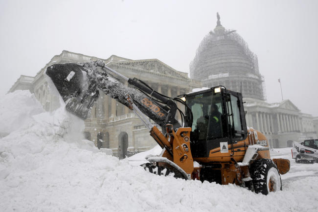 A Capitol Hill employee uses a heavy earth moving machine to clear snow during a winter storm in Washington January 23, 2016. (Joshua Roberts/Reuters)