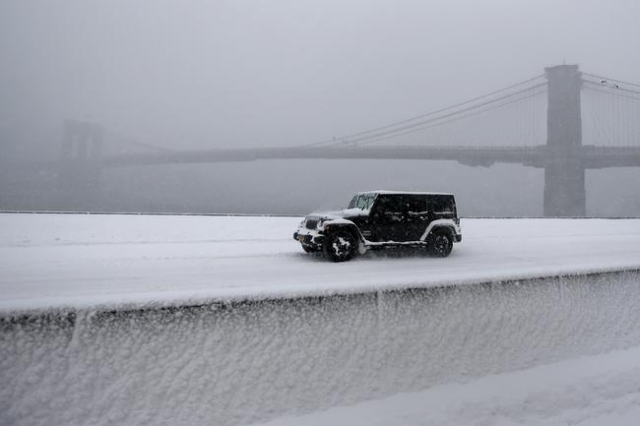 A jeep makes its way north though heavy snow on the FDR Drive with the Brooklyn Bridge in background during a snowstorm in the Manhattan borough of New York, January 23, 2016.     REUTERS/Carlo Al ...
