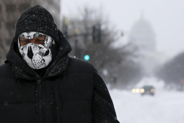 In the shadow of the U.S. Capitol dome, Daniel Pratt walks in the snow to try to find an open store in Washington January 23, 2016. Pratt, who is homeless, is wearing a ski mask that was donated t ...
