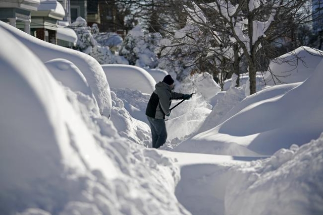 A resident shovels snow away from the entrance to his home in Union City, New Jersey, across the Hudson River from midtown Manhattan, after the second-biggest winter storm in New York history, Jan ...