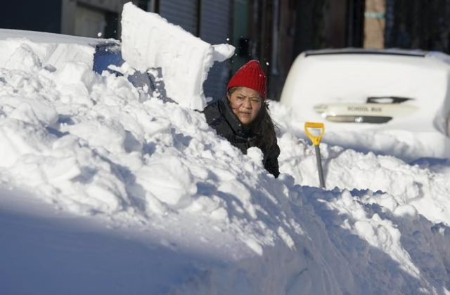 A resident digs her car out from the snow in Union City, New Jersey, across the Hudson River from midtown Manhattan, after the second-biggest winter storm in New York history, January 24, 2016. (R ...