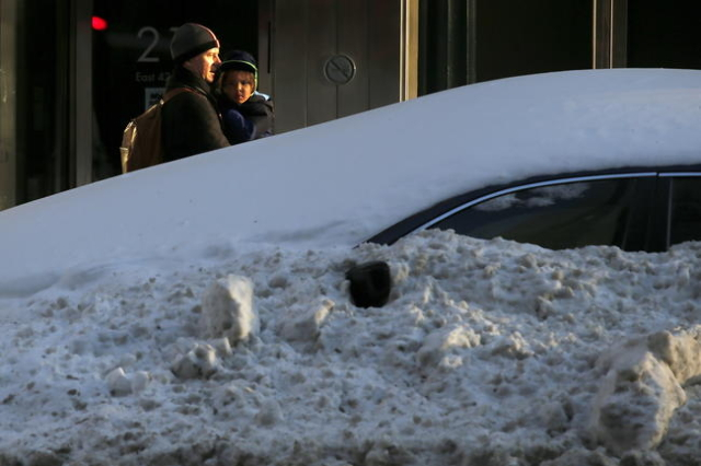 A man holds a child as he passes a snow-encased car on 42nd Street in the Manhattan borough of New York, Jan. 25, 2016. (Carlo Allegri/Reuters)
