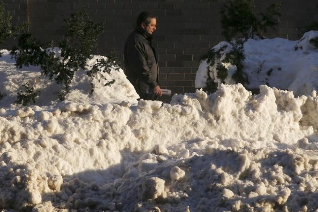 A man walks along 42nd Street past a snow bank in the Manhattan borough of New York, January 25, 2016. (Carlo Allegri/Reuters)
