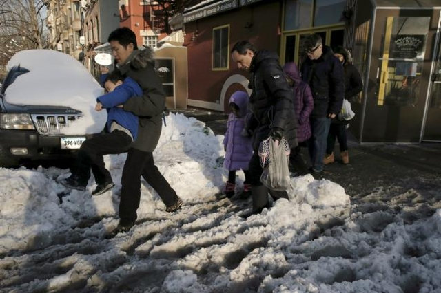 People navigate through the snow and slush during the morning commute in the Brooklyn borough of New York, January 25, 2016. (Brendan McDermid/Reuters)