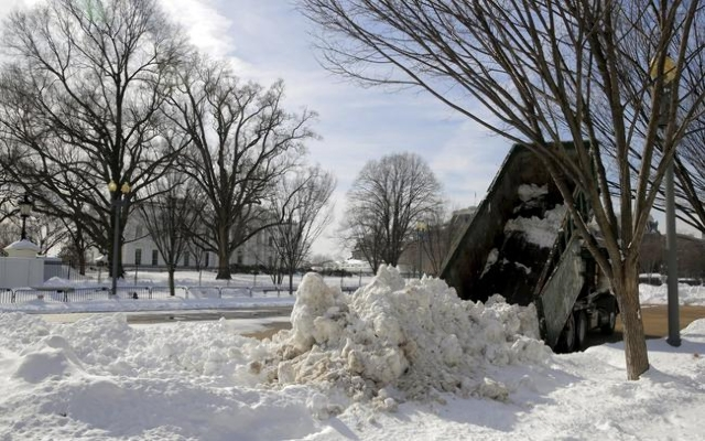 A dump truck piles a load of snow in front of the White House after a major winter storm swept over Washington January 25, 2016.  (Joshua Roberts/Reuters)