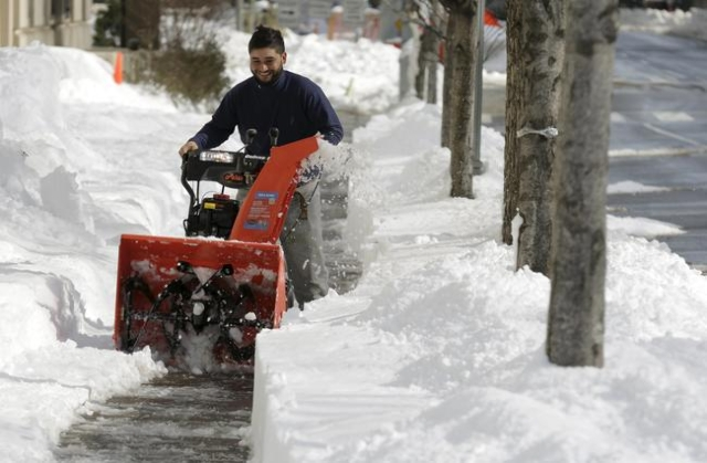 A man uses a snow blower to clear a sidewalk after a major winter storm swept over Washington, Jan. 25, 2016. (Joshua Roberts/Reuters)