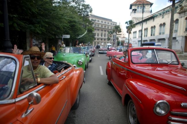 Tourists enjoy a ride in vintage cars in old Havana in this January 17, 2016 picture. REUTERS/Alexandre Meneghini