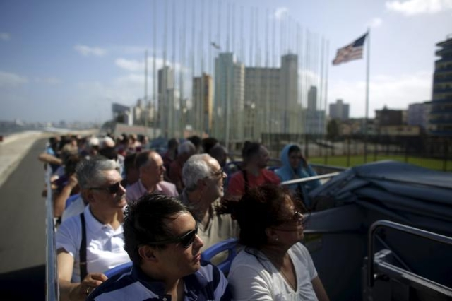 Tourists look at the U.S. Embassy from the top of a double decker sightseeing bus in Havana, in this January 17, 2016 picture. REUTERS/Alexandre Meneghini