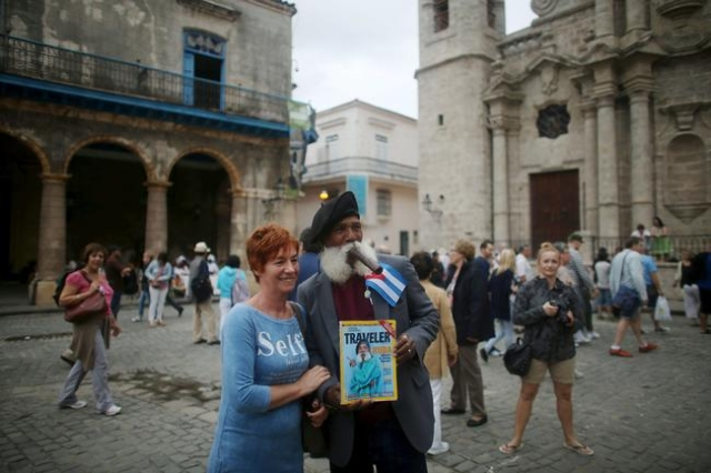 Hermenegildo Arensivia, 61, (R), takes a picture with a tourist from Poland in old Havana in this January 13, 2016 picture. REUTERS/Alexandre Meneghini