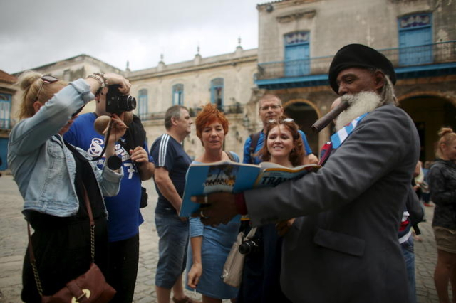 Hermenegildo Arensivia, 61, (R), shows pictures of him in a magazine to tourists from Poland in old Havana in this January 13, 2016 picture. REUTERS/Alexandre Meneghini