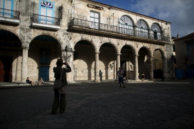 A tourist takes pictures at the Cathedral Square in old Havana in this January 17, 2016 picture. REUTERS/Alexandre Meneghini