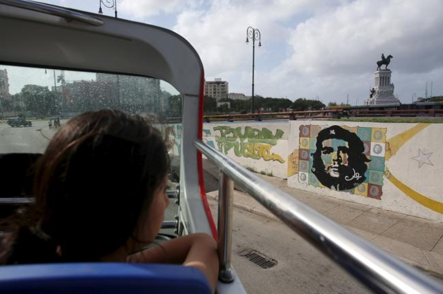 "A tourist from Peru looks at a graffiti of revolutionary hero Ernesto ""Che"" Guevara from the top of a double decker sightseeing bus in Havana in this January 17, 2016 picture. REUTERS/Al ..."