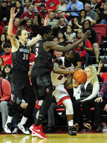 San Diego State forwards Matt Shrigley and Angelo Chol (3) defend UNLV guard Ike Nwamu (0) in the second half of their NCAA college basketball game  at the Thomas & Mack Center in Las Vegas Sa ...
