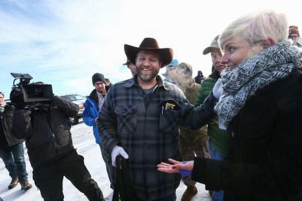 Ammon Bundy, center, reacts after receiving vegan jerky from PETA spokeswoman Lindsay Rajt after a news conference by the entrance of Malheur National Wildlife Refuge headquarters near Burns, Ore. ...
