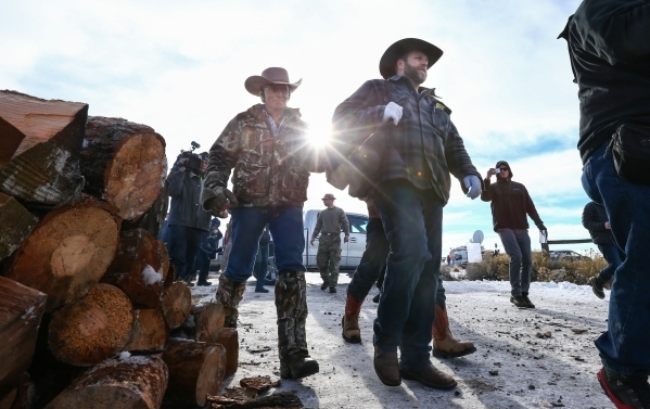 Ammon Bundy, right, walks with Arizona rancher LaVoy Finicum after a news conference by the entrance of Malheur National Wildlife Refuge headquarters near Burns, Ore. on Wednesday, Jan. 6, 2016. ( ...