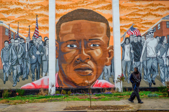 A man walks past a mural of Freddie Gray in the Sandtown-Winchester neighborhood of Baltimore, Dec. 17, 2015. (Bryan Woolston/Reuters)