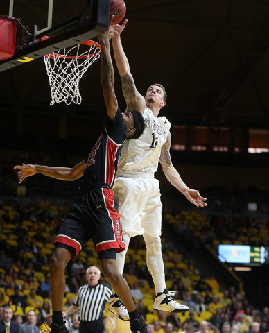 Wyoming's Josh Adams blocks a shot by UNLV's Patrick McCaw in the first half Saturday, Jan. 9, 2016, at Arena-Auditorium in Laramie, Wyo. (Blaine McCartney/Wyoming Tribune Eagle)