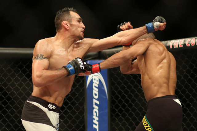 Tony Ferguson (blue gloves) throws a punch at Edson Barboza (red gloves) during The Ultimate Fighter Finale at The Chelsea in The Cosmopolitan of Las Vegas on Friday, Dec. 11, 2015. Ferguson won b ...