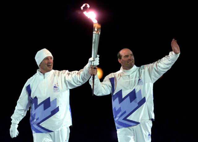 Former U.S alpine skiers Bill Johnson, left, and Phil Mahre carry the Olympic torch during the opening ceremony of the Salt Lake 2002 Winter Olympic Games, Feb. 8, 2002. (Shaun Best/Reuters)
