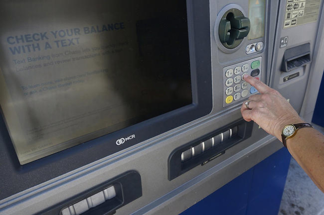 A woman withdraws cash from a Chase drive-up Automated Teller Machine, or ATM. (CNN)