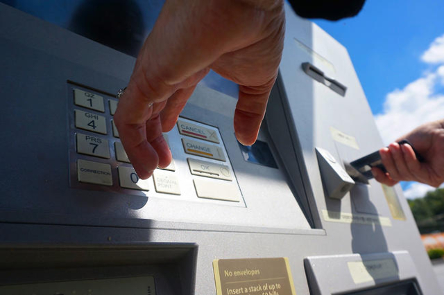 A woman uses a Wells Fargo walk-up Automated Teller Machine, or ATM. (CNN)