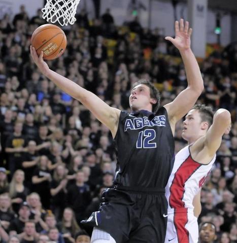 Utah State forward Lew Evans (12) drives to the basket as UNLV forward Stephen Zimmerman Jr. (33) defends, Tuesday, Jan. 19, 2016, in Logan, Utah. (Eli Lucero/Herald Journal)